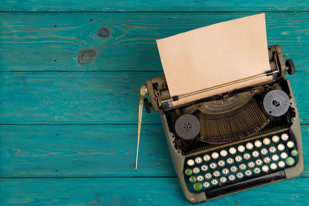 Vintage typewriter on the blue wooden desk